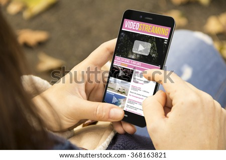 video streaming concept: woman holding a 3d generated smartphone with video website on the screen. Graphics on screen are made up. - stock photo
