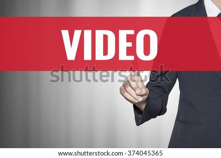 Video word on virtual screen push by business woman red tab - stock photo