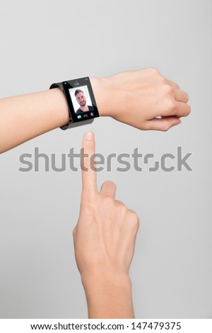 Videochat with a modern Internet Smart Watch on grey background On the screen you can see a videochat. All Texts, Icons, Computer Interfaces of the Smart Watch where created from scratch by myself. - stock photo