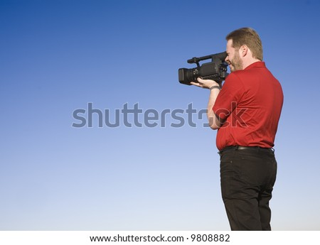 Videographer shooting handheld footage with prosumer camcorder, shot against blue sky. - stock photo