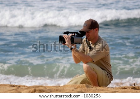 Videographer shoots on Oahu's North Shore. (image contains noise) - stock photo