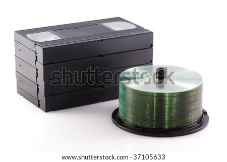 Videotapes and a pile of DVDs on a white background. - stock photo