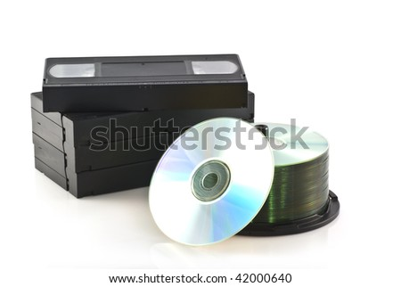 Videotapes and a pile of DVDs on a white background.