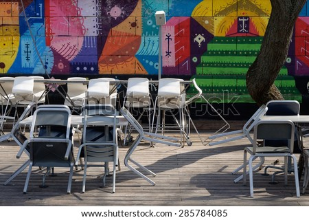 VIENNA, AUSTRIA - April 13, 2015: Outdoor restaurant before opening in spring, graffiti wall background, Danube Canal (Donaukanal), Vienna.