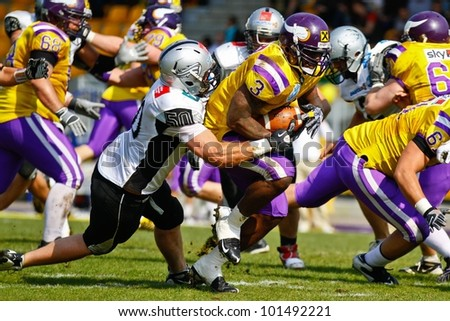 VIENNA, AUSTRIA - APRIL 17 RB Tony Hunt (#3 Vikings) is tackled by DL Mario Rinner (#50 Raiders) on April 17, 2011 in Vienna, Austria. The Vienna Vikings beat the Swarco Raiders 28:24. - stock photo