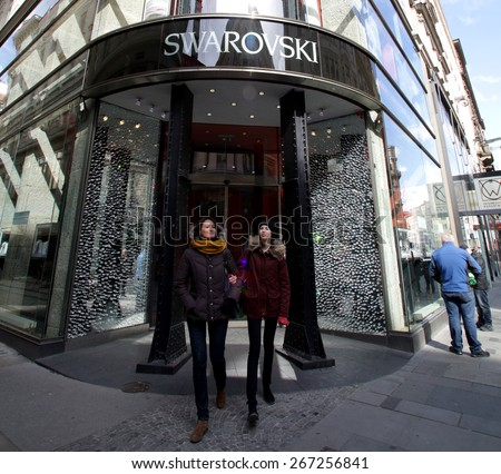 VIENNA, AUSTRIA - APRIL 6, 2015: Shoppers exit a Swarovski crystal retail store. Swarovski AG is an Austrian producer of luxury cut lead glass. - stock photo