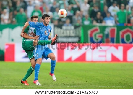 VIENNA, AUSTRIA - AUGUST 22 Christopher Trimmel (#28 Rapid) and Giorig Guruli (#6 Dila Gori) fight for the ball at a UEFA Europa League game on August 22, 2013 in Vienna, Austria. - stock photo