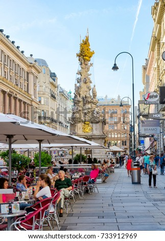 VIENNA, AUSTRIA - AUGUST 28: People at a restaurant in the pedestrian area of Vienna, Austria on August 28, 2017. Foto with view to the baroque Plague column.