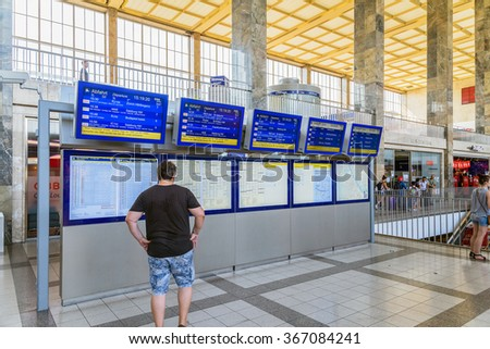 VIENNA, AUSTRIA - AUGUST 08, 2015: People Looking At Departure And Arrivals Screens In Wien Mitte Station The Major Hub For S-Bahn Suburban Trains, U-Bahn Trains And The City Airport Train (CAT). - stock photo