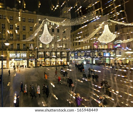 VIENNA, AUSTRIA - DECEMBER 4: Many people are shopping on the Graben in the evening on December 4, 2013 in Vienna, Austria. The Graben is one of the most famous streets in Vienna's first district. - stock photo