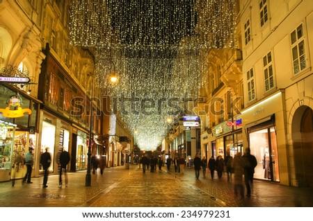 VIENNA, AUSTRIA - December 11, 2009: Vienna -  street at night with tourists and Christmas chandeliers in Vienna, Austria. on December 11, 2009 - stock photo