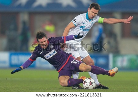 VIENNA, AUSTRIA - DEZEMBER 11 Konstantin Zyryanov (#18 Zenit) and Marko Stankovic (#19 Austria) fight for the ball at a UEFA Champions League game on Dezember 11, 2013 in Vienna, Austria. - stock photo