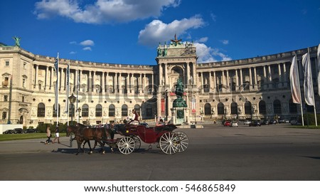 Vienna, Austria, July 29, 2016: Hofburg palace and panoramic square view, people walking and fiaker with white horses in Vienna, Austria.