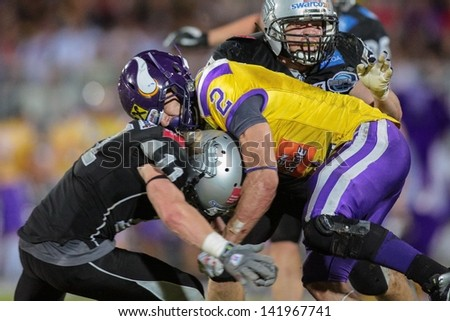 VIENNA, AUSTRIA - JULY 28 RB Dusty Thornhill (#2 Vikings) is tackled by DB Enrico Martini (#11 Raiders) on July 28, 2012 in Vienna, Austria. - stock photo