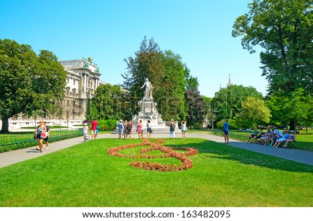 VIENNA, AUSTRIA - JULY 28: Tourists visit the monument to Mozart on July 28, 2013 in Vienna, Austria. The Mozart monument in Vienna was built by the sculptor Viktor Tilgner in 1896.  - stock photo