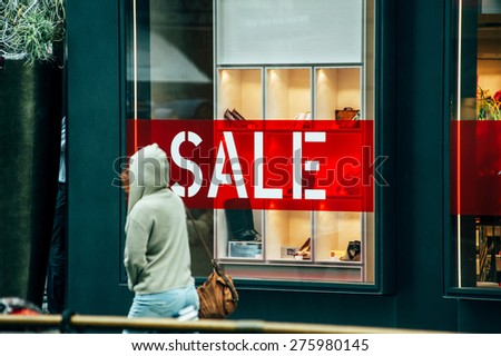 VIENNA, AUSTRIA - JULY 05, 2011: Woman passing in front of large window of luxury store with red on white letters SALE. Vienna is a magnetic attraction for tourists from across the world  - stock photo