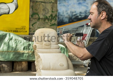 Vienna, Austria. June 2015 - An Artist working on a sculpture at the Danube Canal - stock photo