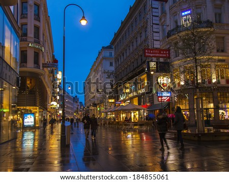 Vienna, Austria, March 23, 2014. Tourists walk on the evening streets in rainy weather