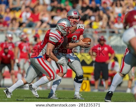 VIENNA, AUSTRIA - MAY 26, 2014: QB Christoph Gross (#8 Austria) hands off the ball to RB Florian Pos (#26 Austria) in match against Denmark during the EFAF European Championships 2014 in Austria. - stock photo