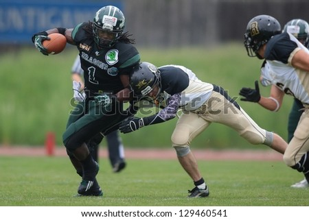 VIENNA, AUSTRIA - MAY 12:  RB Tunde Ogun (#1 Dragons) is tackled on May 12, 2012 in Vienna, Austria. - stock photo