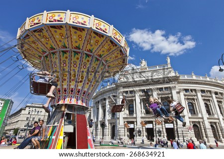 VIENNA, AUSTRIA - MAY 26, 2012: The historic Burgtheater (Imperial Court Theatre) at the famous Wiener Ringstrasse with some people enjoy a ride on a old-fashioned style Carousel on a sunny day. - stock photo