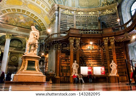 VIENNA, AUSTRIA - MAY 30: Tourists and the visitors of the Austrian National Library admire the luxurious interior on May 30 , 2013 in Vienna. The largest library in Austria with 7.4 million items. - stock photo