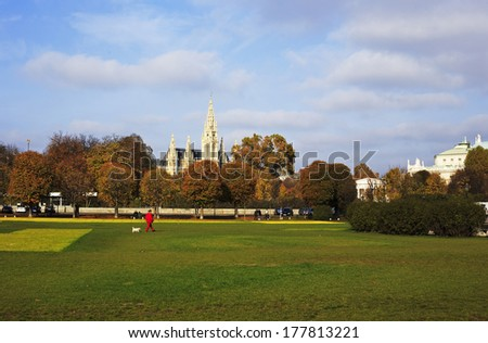 VIENNA, AUSTRIA - NOVEMBER 1: Picture of a park in Vienna, with Wiener Rathaus (Vienna City Hall) in the background on November 1, 2013. A red-dressed woman is walking with her white dog.