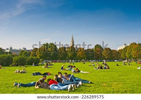 VIENNA, AUSTRIA - OCTOBER 12, 2014: Young people relaxing in a park in Vienna near City Hall - stock photo