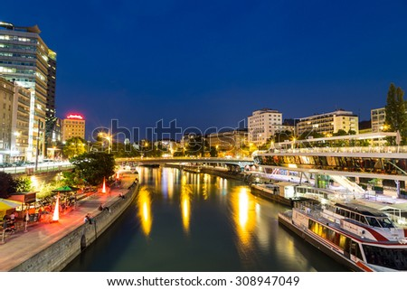 VIENNA, AUSTRIA - 21ST AUGUST 2015: A view along the Danube Canal during the blue hour. People, buildings, bars and boats can be seen. - stock photo