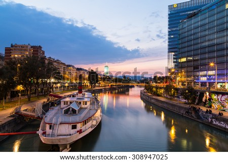 VIENNA, AUSTRIA - 21ST AUGUST 2015: A view along the Danube Canal shortly after sunset. People, buildings and bars can be seen. - stock photo