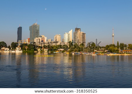 VIENNA, AUSTRIA - 1ST SEPTEMBER 2015: Buildings near Danau Park in Vienna in the morning. People can be seen rowing in the water.