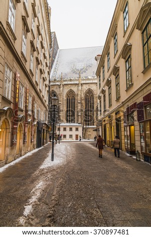 VIENNA, AUSTRIA - 5TH JANUARY 2016: Part of St. Stephen's Cathedral (Stephansdom) in Vienna from Churhausgasse during the winter. Snow can be seen on the building. People can be seen. - stock photo