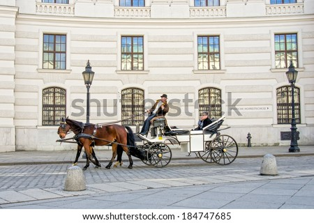 VIENNA - FEBRUARY 14: Tourists enjoy  the ride in a horse-drawn carriage around the Hofburg Palace on Feb 14, 2014 in Vienna.