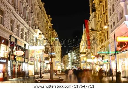VIENNA- MAR 15: People go on main pedestrian street Kartner Strasse at night on March 15, 2012 in Vienna, Austria. Vienna Kartner Strasse street is the main shopping street in Vienna. - stock photo