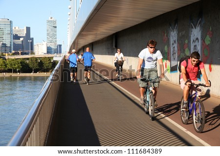VIENNA - SEPTEMBER 6: Pedestrians walk and cyclists ride on September 6, 2011 in Danube river bridge, Vienna. Vienna is often quoted among most bicycle and pedestrian friendly cities. - stock photo