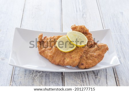 Viennese Schnitzel with lemon slices on a plate - stock photo