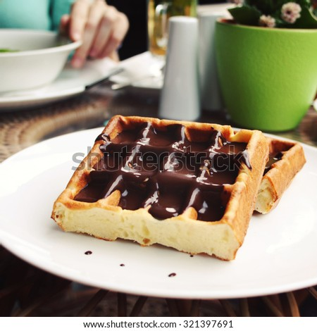 Viennese Waffles covered with chocolate. Aged photo. Vienna Waffles covered with chocolate topping. White plate with sweet food. - stock photo