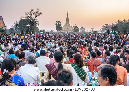VIENTIANE, LAOS - NOV 21: A thousands of Lao people assembled to give offering to Buddhists monks early in the morning on Nov 21, 2010 during That Luang Festival is held on the full moon in Nov every year. - stock photo