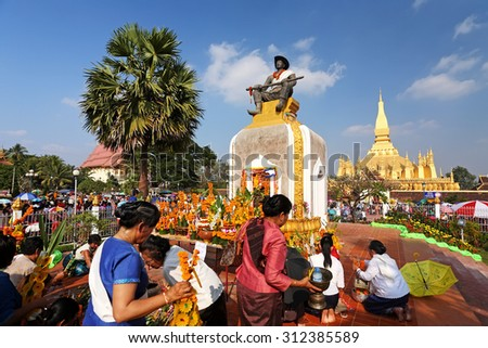 VIENTIANE, LAOS - NOV 20: Unidentified many people praying statue of the King Chao Anouvong in front of the Pha That Luang on Nov 20, 2010 It is celebrated 450th year founding anniversary of Vientiane - stock photo