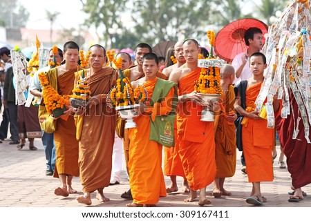 VIENTIANE, LAOS - NOV 20 : Unidentified monks phan holding flowers arranged in lotus-shape walk around Pha That Luang on Nov 20, 2010 It is celebrated 450th year founding anniversary of Vientiane - stock photo