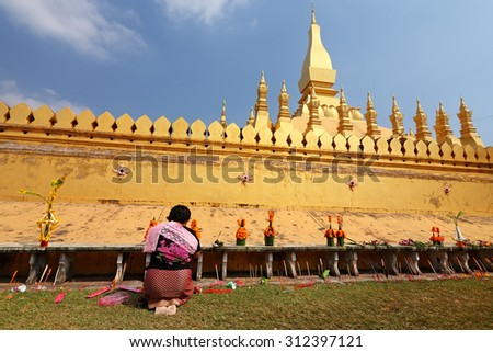 VIENTIANE, LAOS - NOV 20: Unidentified people praying in front of the Pha That Luang on Nov 20, 2010 It is celebrated 450th year founding anniversary of Vientiane - stock photo