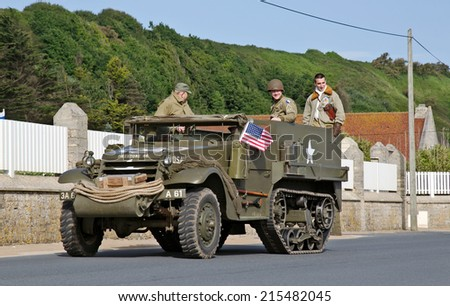 VIERVILLE, FRANCE - JUNE 5: A US army WW2 halftrack passes along Omaha beach in prelude to the gathering of a large military vehicle convoy celebrating the D-Day landings on June 5, 2014 in Vierville - stock photo