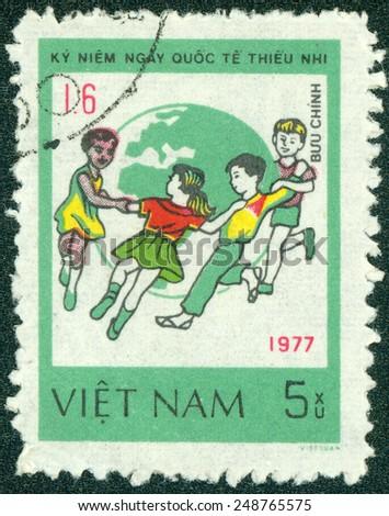 VIETNAM - CIRCA 1980: Postage stamp printed in Vietnam, dedicated to International Children's Day (1977), shows Children dance around Globe, circa 1980 - stock photo