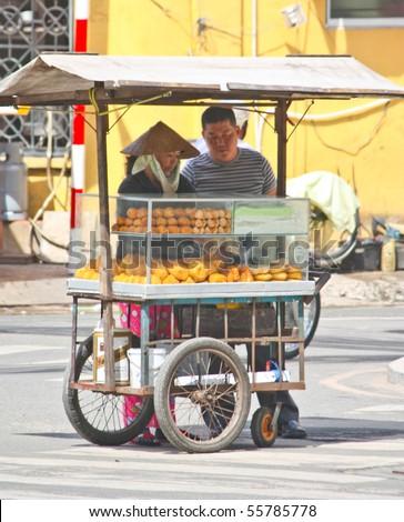 VIETNAM - JUNE 10 : A Vietnamese bread stall vendor sells bread along the road side. June 10, 2010 Ho Chi Minh City, Vietnam - stock photo