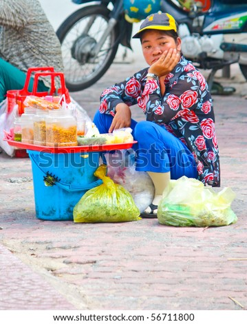 VIETNAM - JUNE 10: A Vietnamese street food vendor having a depressed look while sitting on the road side. June 10, 2010 Ho Chi Minh City, Vietnam