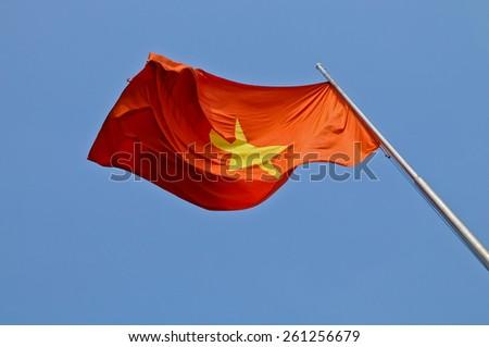 Vietnam national flag flying in blue sky - stock photo