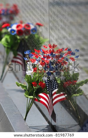 Vietnam Wall Memorial Flowers and Flag in Washington, DC - stock photo