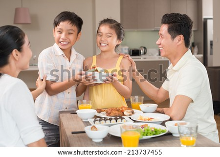 Vietnamese boy helping his little sister to serve the family dinner table - stock photo