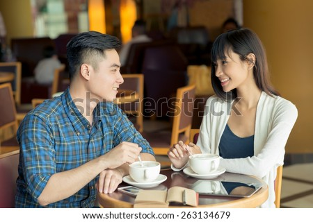 Vietnamese business couple having lunch in a cafe