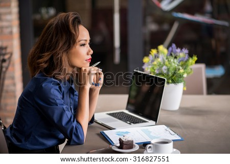 Vietnamese business lady pondering over ideas for new business project - stock photo